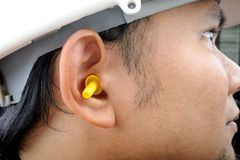 Ear plugs. Closeup yellow ear plug isolated into the ear royalty free stock images