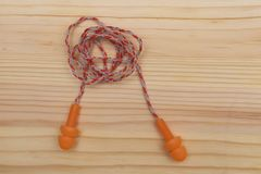 Ear plugs with cord. Ear plugs with cord on wooden background royalty free stock image