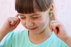 Ear plugs to protect against the noise. Girl covered her ears royalty free stock photo