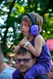 Ear-protection, Father with his child with big purple headphones Royalty Free Stock Photography