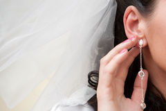 Ear-ring. A girl touching her ear-ring stock image