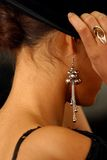 Ear rings. The image of the girl in rings and ear rings putting on a hat Royalty Free Stock Photography