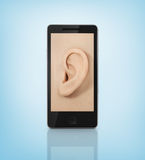 Ear to the phone screen. Royalty Free Stock Images
