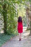 Ear view of woman in red, high heels and cocktail dress in wood Royalty Free Stock Image