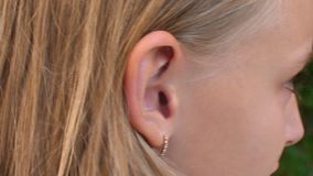 Ear of young blonde girl with golden earring, close up. View. Female child with earring in ear, cropped view stock footage
