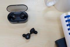 Earbuds e caricatore senza fili sulla tavola in ufficio fotografia stock libera da diritti