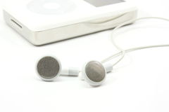 Earbuds next to MP3 Player. Earbuds next to a MP3 player on a white background Royalty Free Stock Image