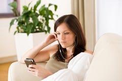 earbuds som rymmer den lyssnande musikspelarekvinnan Arkivfoto