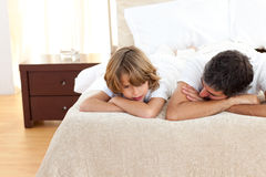 Earing father talking with his son lying on bed Royalty Free Stock Photography