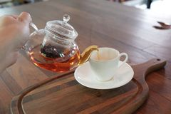 Earl Grey tea in glass tea pot on wood plate with white cup. stock images