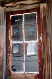 Early 1900 Hotel Reflected in Ghost Town Window. Vertical image of the reflection of an early 1900's hotel reflected in a decaying window of an American Western Royalty Free Stock Images