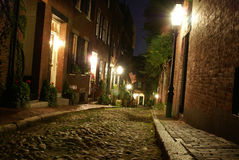 Early america1. Old 19th Century cobble stone road in Boston Massachusetts, lit only by the gas lamps revealing the shuttered windows and brightly lit doorways Stock Photos