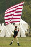 An early American flag is flown by solider on his way to Surrender Field at the 225th Anniversary of the Victory at Yorktown, a re. Enactment of the siege of Stock Photo