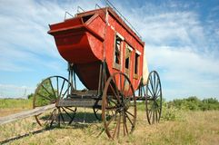 Early American Stagecoach. Restored early American stagecoach against blue sky background Stock Photo