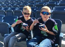 Children eating ice cream at empty baseball park. Early arrival at baseball park to get the best seats these young twin brothers enjoy a bowl of ice cream. Empty royalty free stock images