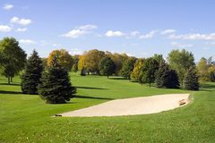 Early Autumn Golf. A cool autumn day on the golf course the leaves just starting to turn colors in Wisconsin. The bunker ahead awaits your ball Royalty Free Stock Photo