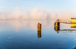 Lone fisherman on a river dock in the early autumn morning Stock Photo