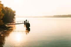 Lone fisherman on the riverbank in the early autumn morning Stock Image