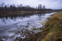 Early autumn on the river. River, frozen grass, the first snow Royalty Free Stock Photos