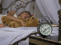 Early awakening. Alarm clock standing on bedside table. Wake up of an asleep young girl holding teddy bear in bed on a. Background Stock Photography