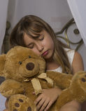Early awakening. Alarm clock standing on bedside table. Wake up of an asleep young girl holding teddy bear in bed on a Stock Image