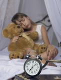 Early awakening. Alarm clock standing on bedside table. Wake up of an asleep young girl holding teddy bear in bed on a. Background Royalty Free Stock Photos