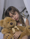 Early awakening. Alarm clock standing on bedside table. Wake up of an asleep young girl holding teddy bear in bed on a. Background Royalty Free Stock Photo