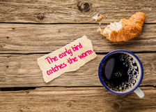 The early bird catches the worm. An inspirational saying hand written on a small torn piece of paper alongside an early breakfast of frothy espresso coffee and stock images