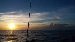 Early bird gets the bite. Fishing rod ahead of sunrise Stock Photo