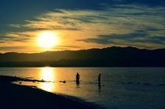 Early Birds. At the break of dawn, I came across this two people gathering mussels for a living Stock Photography
