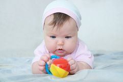 Early brain development. concentrated little baby girl playing with rattle royalty free stock image