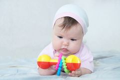 Early brain development. concentrated little baby girl playing with rattle. Lying on bed royalty free stock photography