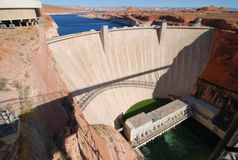 Early Centry Dam. Glen Canyon Dam with Powell Lake in the background and the Colorado River running through.  The dam's main purpose includes generating Stock Photos