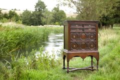 Early chest of drawers on stand in field by a river Royalty Free Stock Photography