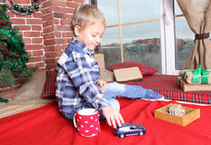 Early child development. Very pretty boy sitting near the window and play with toys. He is dressed in jeans and a shirt Stock Images