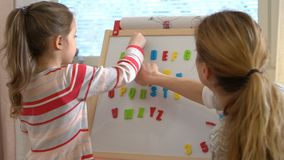Early childhood development. Young woman teaching her child the alphabet. Early childhood development. Little girl are learning to write letters with special stock video footage
