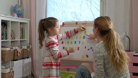 Early childhood development. Young woman teaching her child the alphabet. Early childhood development. Little girl are learning to write letters with special stock video