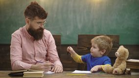 Early Childhood Education and Playing Concept. Dad with son drawing. Daddy with little boy making drawings. School stock footage