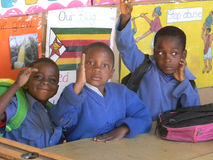Early childhood education pupils in class. Norton,Zimbabwe,July 18 2015. Early childhood education students with hands up in a in classroom.Zimbabwe's education stock image