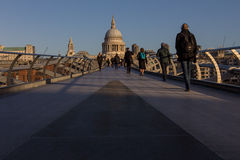 Early commuters. Commuters walking on the Millennium footbridge in the early morning sunshine before the rush hour, towards St Paul's Cathedral, London, England Stock Image