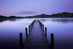 Early dawn on lake. A pier or jetty and quiet lake in early pre-dawn light stock photo