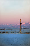 Early dawn with an oil rig and Rocky Mountains Stock Image