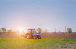 Early, at dawn on a spring morning tractor lit by the rays of the sun, Royalty Free Stock Image