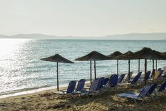 Morning at a beach with loungers under palm tree leaves umbrellas. Ierissos, Greece. Early day at beautiful Ierissos beach in Greece with loungers under palm royalty free stock image