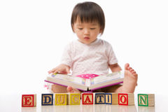 Early education. Word education with little girl on background reading a book. *** Main focus on EDUCATION word block Royalty Free Stock Photo
