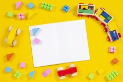 Early education background. Wooden train, car, colorful bricks and blocks with open blank notebook on yellow background royalty free stock photo