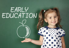 Early education concept, child girl near school blackboard Stock Photo