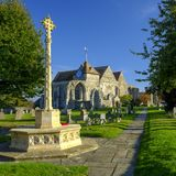 Early evening autumn light on St Thomas the Martyr church and village cross, Winchelsea, East Sussex, UK royalty free stock image