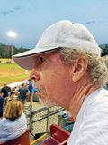 Older man with goatee, curly grey hair and white cap at baseball royalty free stock images