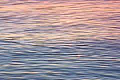 Early evening sun shimmering on calm water. With an orange and pink glow royalty free stock images